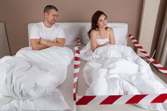 Angry young woman lying separately from husband on the bed Royalty Free Stock Image