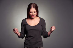 Angry young woman over dark background Royalty Free Stock Image