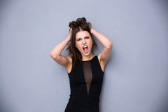 Angry young woman over gray background Stock Image
