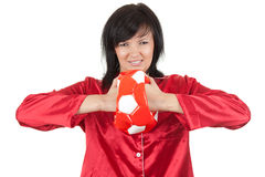 Angry young woman in red pyjama with ball Stock Photos