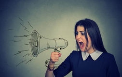 Angry young woman screaming in megaphone Royalty Free Stock Photography