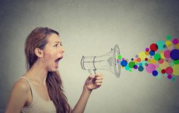 Angry young woman screaming in megaphone Royalty Free Stock Images