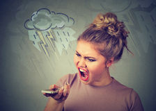 Angry young woman screaming on mobile phone Stock Images