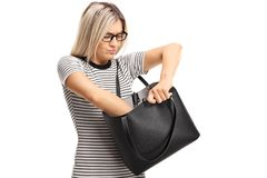 Angry young woman searching in her handbag. Isolated on white background stock image