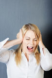Angry Young Woman Shouting While Covering Ears Royalty Free Stock Photo