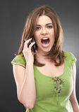 Angry young woman shouting on mobile phone stock photos