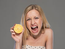 Angry young woman showing lemon Royalty Free Stock Photography
