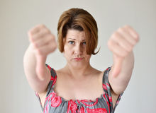 Angry young woman showing thumb down Royalty Free Stock Images
