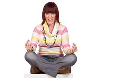 Angry young woman sitting cross-legged, isolated. Angry screaming young woman sitting cross-legged trying to meditate, isolated on white Royalty Free Stock Photo