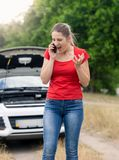 Angry young woman standing at broken car in field and shouting in mobile phone. Angry woman standing at broken car in field and shouting in mobile phone royalty free stock photo
