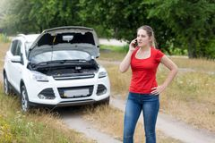 Angry young woman standing at her broken car in field and talking by phone with mechanic Stock Photos