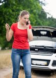 Portrait of angry young woman talking by phone and calling assistance to her broken car in field Stock Image