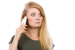 Angry young woman talking on phone. Unpleasant conversation, bad relationships concept. Angry young blonde woman talking on phone Royalty Free Stock Photos