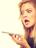 Angry young woman talking on phone. Unpleasant conversation, bad relationships concept. Screaming furiously angry young blonde woman talking on phone Royalty Free Stock Images