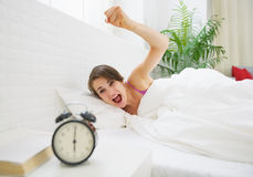 Angry young woman wants to break awakened her alarm clock Stock Photo