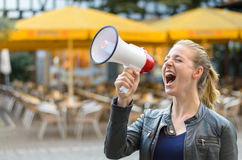 Angry young woman yelling into a megaphone Royalty Free Stock Photo