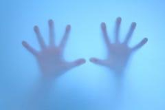 Angst aangejaagde handen op berijpt glas stock afbeelding