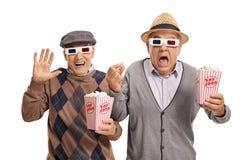 Angst aangejaagde oudsten met 3D glazen en popcorn Stock Foto's