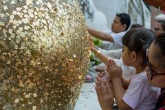 Angthong/Tailândia - 29 de maio de 2018: a menina reza em buddha e doura pela folha de ouro em buddha de bronze, em Tailândia Fotografia de Stock
