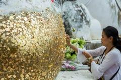 Angthong/Thailand - Mei 29 2018: hand van vrouwen of boeddhistisch gilde door bladgoud op messing Boedha, in Thailand stock afbeelding