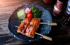 Anguila japonesa asada a la parrilla en pincho fotos de archivo
