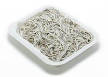 Anguilas jóvenes crudas y x28; eels& x29 del bebé; en bandeja plástica en blanco Imagen de archivo