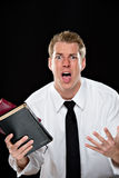 Anguished young man holding bibles Stock Photo