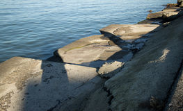 Angular broken concrete slabs at the edge of a calm ocean bay in late afternoon. Royalty Free Stock Images
