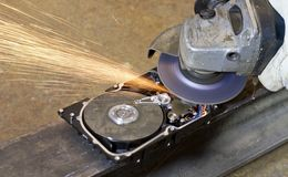 Angular grinder cleaning data from hard drive Stock Image