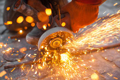 Angular grinding machine cuts metal with sparks. Angular grinding machine cuts metal and sparks Stock Photography