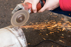 Angular grinding machine cuts metal with sparks.  Royalty Free Stock Images