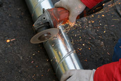 Angular grinding machine cuts metal with sparks.  Royalty Free Stock Photography