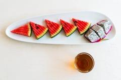 Anguria e frutta affettate del drago sul piatto con tè caldo in Fotografia Stock