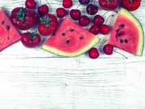 Anguria, fragole e ciliege su fondo di legno Fotografie Stock