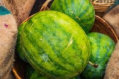 Anguria fresca nelle angurie verdi e gialle del canestro, in Th Immagine Stock Libera da Diritti