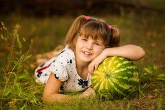 Anguria molto grande felice della tenuta della ragazza del bambino nel giorno soleggiato Concetto sano fotografia stock libera da diritti