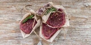 Angus Beef Steaks negro crudo en fondo de madera Carne, especias y Rosemary fotografía de archivo libre de regalías