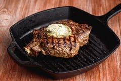 Angus Steak negro asado a la parrilla en la cacerola del hierro de la parrilla en fondo negro de madera Fotografía de archivo libre de regalías