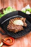 Angus Steak negro asado a la parrilla en la cacerola del hierro de la parrilla en fondo negro de madera Imágenes de archivo libres de regalías