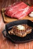 Angus Steak negro asado a la parrilla en la cacerola del hierro de la parrilla en fondo negro de madera Foto de archivo libre de regalías