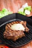Angus Steak negro asado a la parrilla en la cacerola del hierro de la parrilla en fondo negro de madera Fotos de archivo