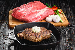 Angus Steak negro asado a la parrilla en la cacerola del hierro de la parrilla en fondo negro de madera con crudo Imagen de archivo