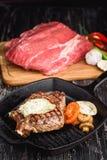 Angus Steak negro asado a la parrilla en la cacerola del hierro de la parrilla en fondo negro de madera con crudo Imagen de archivo libre de regalías