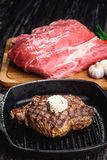 Angus Steak negro asado a la parrilla en la cacerola del hierro de la parrilla en fondo negro de madera con crudo Fotos de archivo libres de regalías