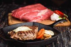Angus Steak negro asado a la parrilla en la cacerola del hierro de la parrilla en fondo negro de madera con crudo Fotografía de archivo