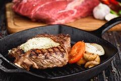 Angus Steak negro asado a la parrilla en la cacerola del hierro de la parrilla en fondo negro de madera con crudo Imagenes de archivo