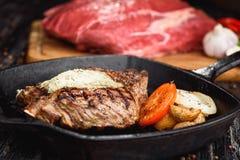 Angus Steak negro asado a la parrilla en la cacerola del hierro de la parrilla en fondo negro de madera con crudo Fotografía de archivo libre de regalías