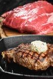 Angus Steak negro asado a la parrilla en la cacerola del hierro de la parrilla en fondo negro de madera con crudo Fotos de archivo