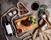 Angus Steak negro asado a la parrilla y un vidrio de vino rojo con los tomates, romero fotografía de archivo libre de regalías