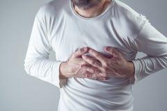 Angustia severa, hombre que sufre de dolor de pecho, teniendo doloroso foto de archivo